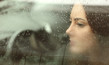 Woman looking out car window on a rainy day