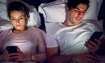 Couple viewing smartphones in bed