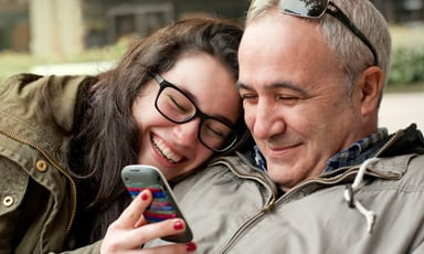 Young woman smiling phone older man
