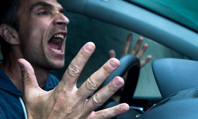 Angry man at steering wheel of car, hands off wheel and gesturing as he yells