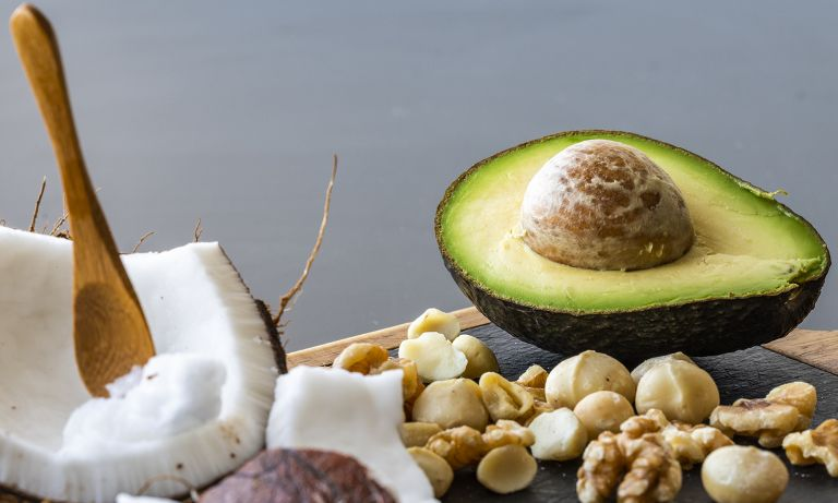 Closeup of section of cutting board with halved avocado, broad wedge of coconut in shell with scoop, macadamia nuts, and walnuts