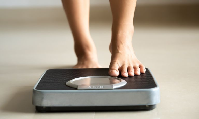 Woman's bare foot steps onto bathroom scale
