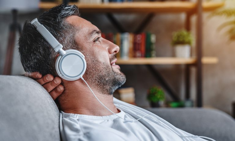 Bearded man sits on sofa, reclining into backrest, back of head resting against hand, smiling and relaxed, headphones on