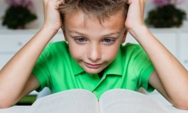 Closeup of young boy anxiously clutching hair on either side of his head with his hands as he looks at opened book