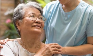 Caregiver places hand on shoulder of elderly women, who reaches her hand to meet it
