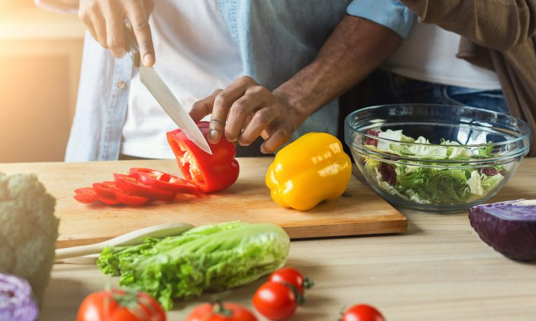 Closeup of bell peppers on cutting board being sliced by man's hands, woman close behind him, other vegetables arrayed on table