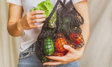 Closeup of mesh satchel full of vegetables slung around a man's shoulders, lettuce in his hand