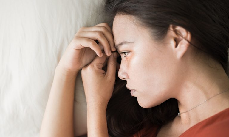 Top view closeup of young woman lying in bed, sad expression, her hands gathered near her forehead