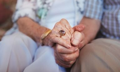 Hands of elderly couple clasped in front of them as they sit side by side