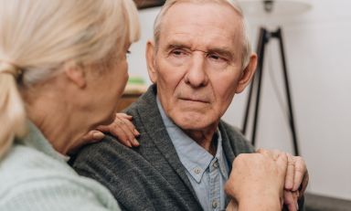 Elderly man, hands clasped over handle of cane, comforted affectionately by his wife