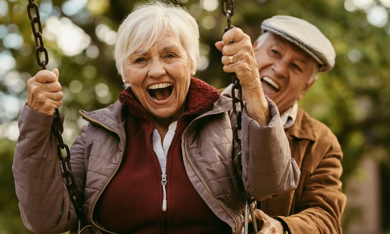 Elderly woman on playground swing, mouth agape in delight as husband gleefully guides swing from behind