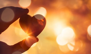 Fingers holding heart emblem, silhouetted in dappled sunlight