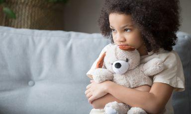 Girl sitting at edge of sofa clutching teddy bear, head tilted down, chin resting on bear's head as she looks forward bashfully