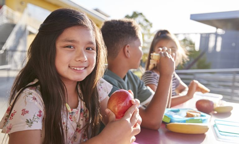 Girl sits with two schoolmates at outdoor lunch table on school grounds, smiling as she holds an apple