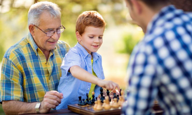 Young boy prepares to grasp a chess piece as he kneels on his grandfather's lap in front of an outdoor chess table