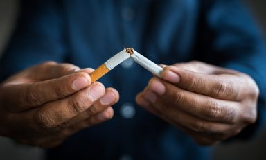 Closeup of a man's hands, each clasping one tip of a cigarette as he breaks it in half