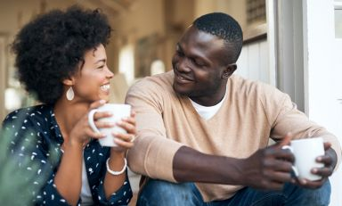 Young woman and man sitting side-by-side on stoop, coffee mugs in hand, looking at each other, smiling