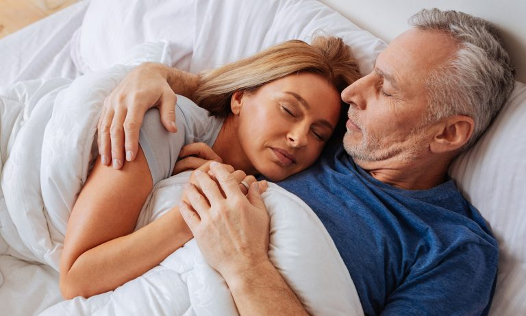 Husband and wife under comforter in bed, cuddling