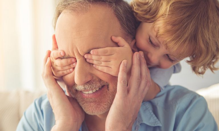 Young child perched on backrest of sofa behind grandpa's head reaches his hands around to cover his grandpa's eyes