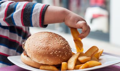 Child grabbing from a stack of large french fry wedges on plate with adult-sized hamburger