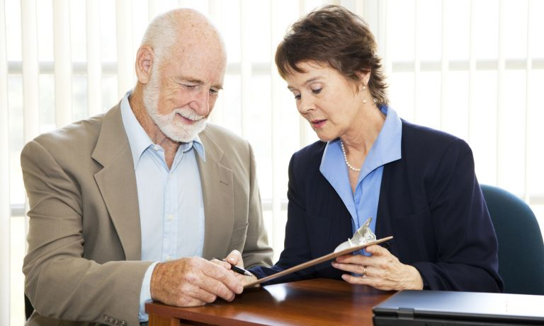 Woman holds clipboard so that document on it faces man beside her in conference room. She explains, using pen to point.