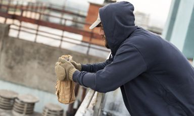 Man wearing hoodie leans forearms on weathered metal outdoor railing, his knit mittens clasping a bottle of liquor in bag