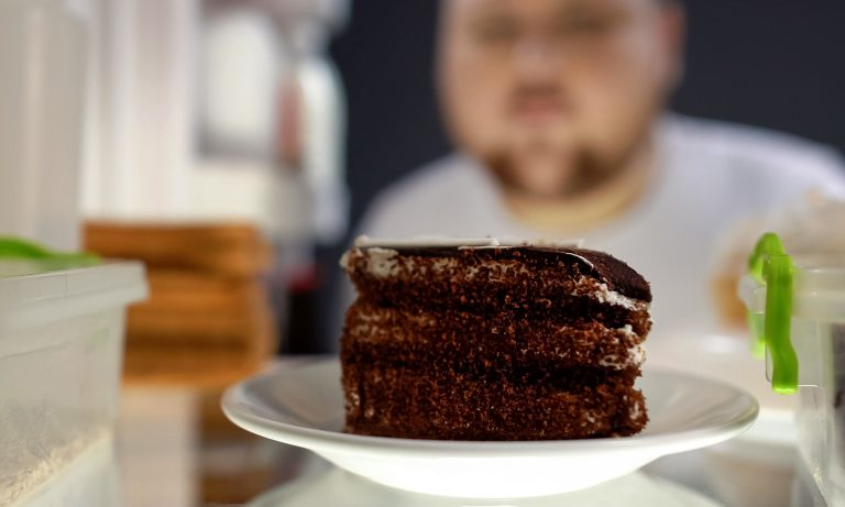 Closeup of slice of chocolate cake in refrigerator, overweight man behind, peering at it from outside