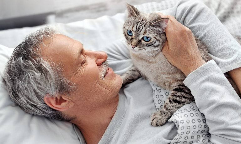 Senior man lying in bed, cradling a cat in his arms and smiling
