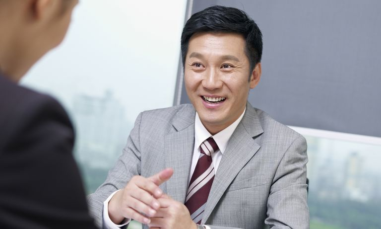 Man in business suit smiling as he gestures while speaking with a cohort across the table, portraits of a downtown skyline behind