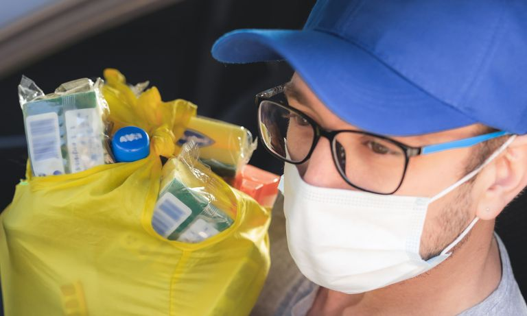 Closeup of man sitting in car's driver's seat, wearing surgical mask and ball cap, holding plastic bag full of groceries