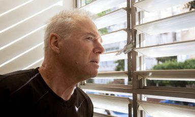 Older man looking out through slats in window blinds towards street warily, his jaw tense
