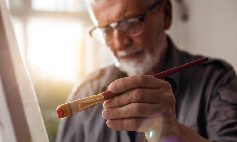 An older man's hand holds a paintbrush as he brings it to the canvas in front of him