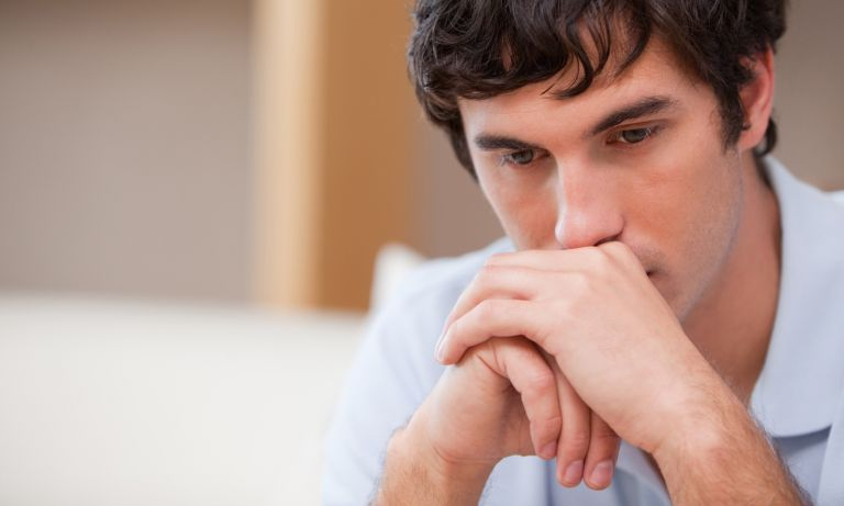 Man resting mouth on hands clasped in front of him, deep in thought