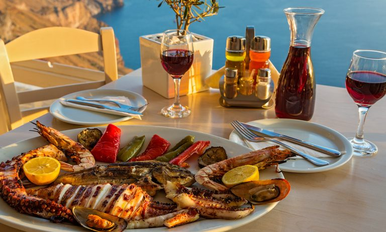 Mediterranean meal on platter with table setting, ocean overlook, seafood, vegetables, red wine served from carafe, olive oil