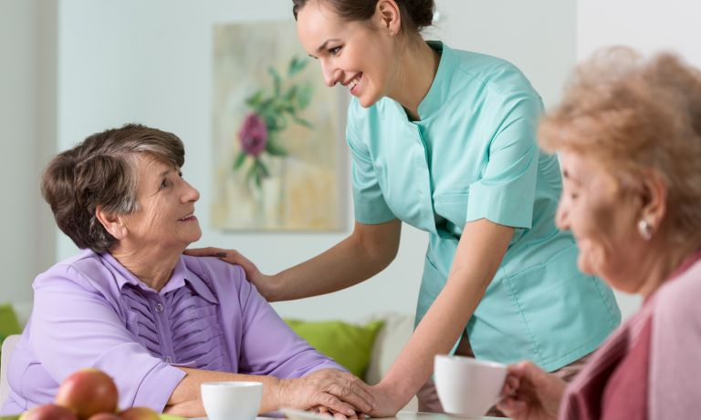 Caring nurse smiling with older lady seated in dining area