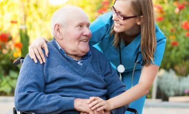 Smiling older man in wheel chair outdoors being affectionately attended to by a medical professional
