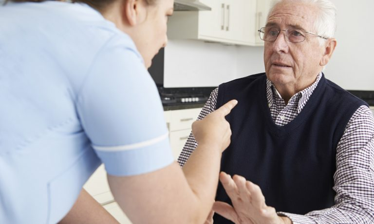 Old man being berated by care worker in his home