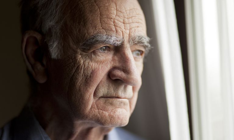 Elderly man gazing out window lost in thought