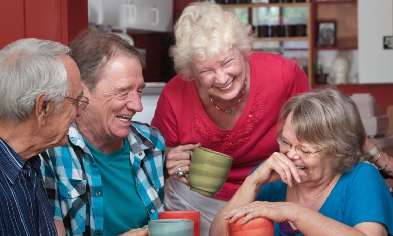 Older friends gathered around kitchen table, clutching ceramic mugs and sharing laughter