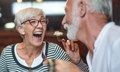 Senior woman laughing while playfully and affectionately feeding her male partner in restaurant