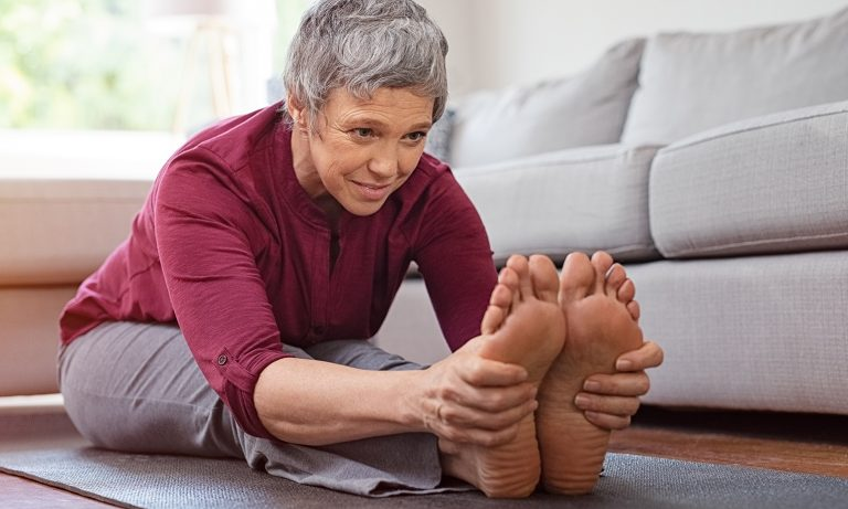 Older woman stretching on mat at home