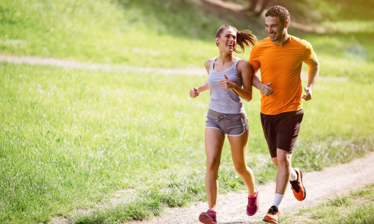 Young couple running along narrow dirt trail in nature area, the woman smiling as she looks at her smiling partner