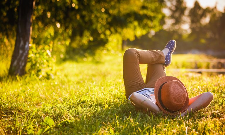 Young person wearing straw hat lying in tree-lined grass field, one bent leg resting on the other, arms folded behind head