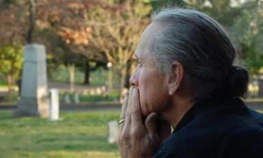 Looking past grief-stricken man in foreground towards gravestones in the distance