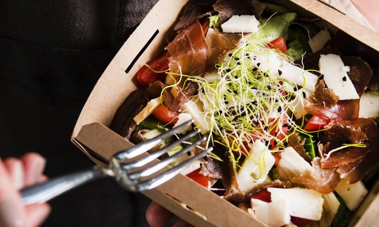 Closeup of salad in takeout box, a fork, grasped in fingers, extending towards it