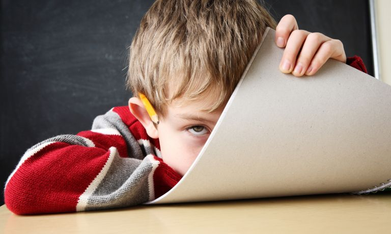 School boy at classroom desk rests his chin on bottom edge of spiral notebook as he bends it towards his face in frustration