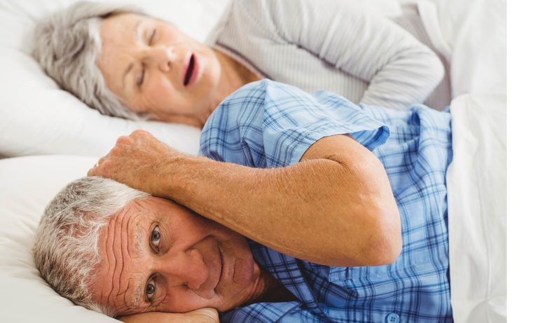 Man covering his ears while wife is snoring