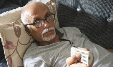 Impassive senior man reclining on couch, clutching remote control in hand as he aims and operates it