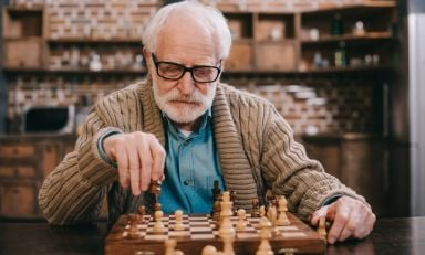 Elderly man at chess table, contemplating his next move
