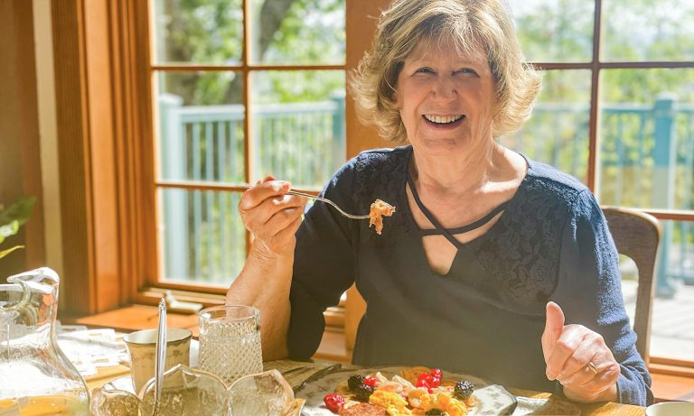 Senior woman enjoying healthy meal at sunlit dining room table at home, picture windows behind her